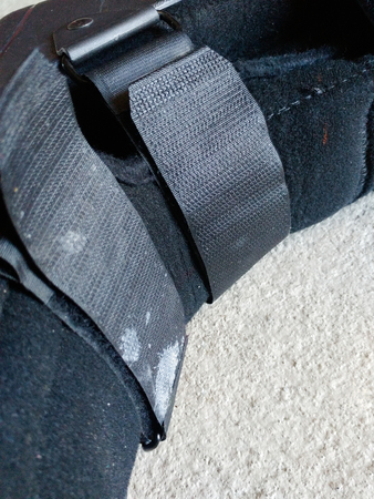 A black Orthopedic or medical boot, cast or footwear, isolated over white, creme concrete, close up view of velcro and straps, white paint splatter on lower strap. Reklamní fotografie