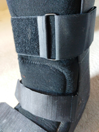 A black Orthopedic or medical boot, cast or footwear, isolated on white or creme colored concrete, closeup view of buckles and straps.