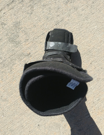 A black Orthopedic or medical boot, cast or footwear, focus looking down into the boot, white paint splatter on buckle, isolated on concrete.