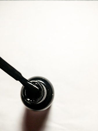 Close up view of black nail polish bottle and brush. White background. Room for text.