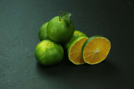 Green sweet tangerines growing with background