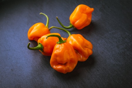 Grouping of raw orange habaneros on a slate surface