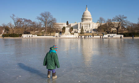 A child standing on the ice of the frozen Reflection Pool behind the Capitol Building in Washington, D.C. in the winter.