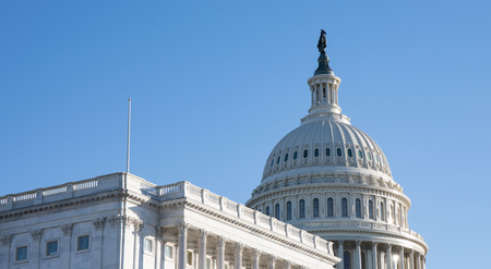 A side view of the Capitol Building in Washington, D.C. with a bright blue sky.