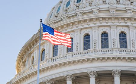 Feche acima da foto da rotunda na construção do Capitólio em Washington, CC com a bandeira americana que voa orgulhosamente.