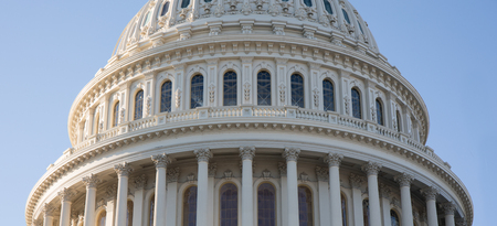 Up close photo of the Capitol Building rotunda in Washington, D.C. with a blue sky.