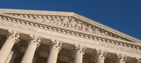 Up close photo of The Supreme Court in Washington, D.C. with a bright blue sky.
