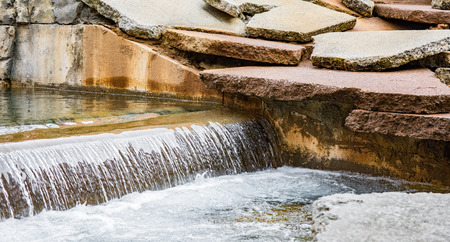 A low waterfall with broken stone slabs on the edge of the canal. Stock Photo