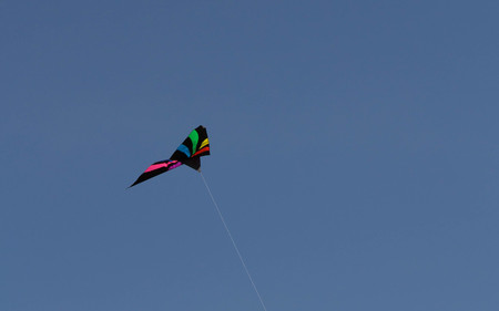 A colorful kite flying in the wind with a bright blue sky.