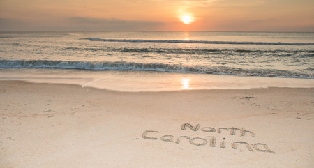 The words North Carolina etched in the sand at sunrise with waves coming ashore.