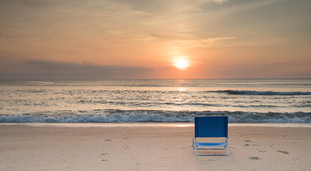 An empty blue beach chair facing the sunrise with waves crashing ashore.