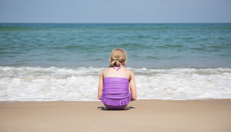 A 9 year old girl crouching in front of the waves coming ashore on the beach. Foto de archivo