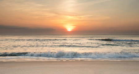 The sun rising over the ocean at sunrise with waves crashing ashore. Stock Photo