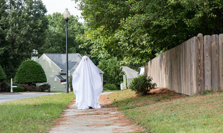 A child in a ghost costume made from a bed sheet walking down the sidewalk toward the camera. Фото со стока
