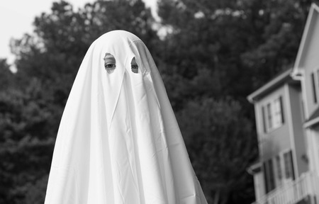 A close up photo of child in a ghost costume made out of a bed sheet.