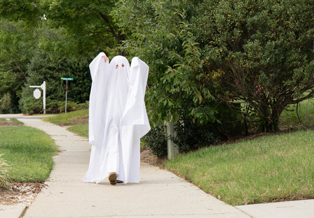 A child in a ghost costume made out of a bedsheet spookily walking down the sidewalk toward the camera. Фото со стока