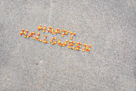 The phrase Happy Halloween spelled out with candy corn on a sidewalk.  The phrase is angled.