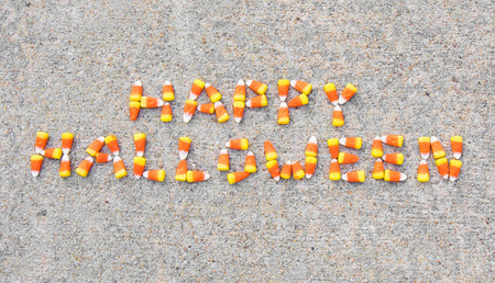 The phrase Happy Halloween spelled out with candy corn on a sidewalk. The phrase is centerd in the photo.
