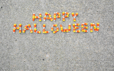 The phrase Happy Halloween spelled out with candy corn on a sidewalk. The phrase is centerd in the top portion of the photo.