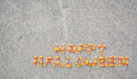 The phrase Happy Halloween spelled out with candy corn on a sidewalk. The phase is located in the bottom right portion of the photo.