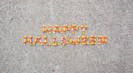 The phrase Happy Halloween spelled out with candy corn on a sidewalk. The phrase is centered in the photo. Archivio Fotografico