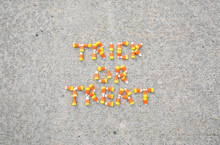 The phrase Trick or Treat spelled out with candy corn on a sidewalk.  The phrase is centered in the photo. Фото со стока