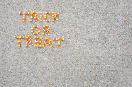 The phrase Trick or Treat spelled out with candy corn on a sidewalk. The phrase is in the upper left corner of the photo.