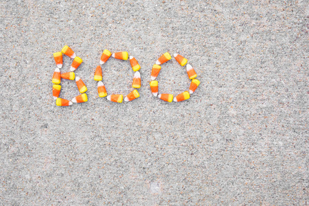 The word Boo spelled out in candy corn on a sidewalk.  The word is in the upper left corner. Archivio Fotografico