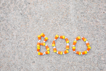 The word Boo spelled out in candy corn on a sidewalk.  The word is in the lower right corner.