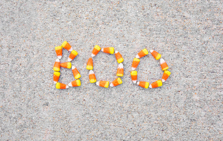 The word Boo spelled out in candy corn on a sidewalk.  The word is centered in the photo. Фото со стока