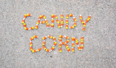 The words Candy Corn spelled out with candy corn on a sidewalk.  The words are centered in the photo.
