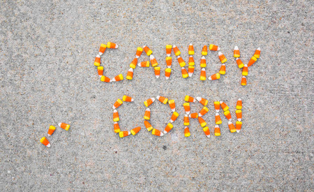 The words Candy Corn spelled out with candy corn on a sidewalk with three extra candy corns beside the words.