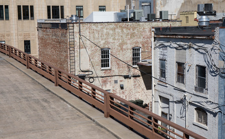 View of the back of buildings on an alleyway from an elevated parking garage.