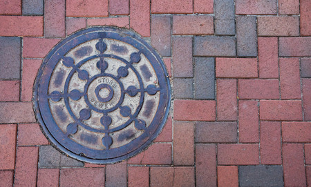 Close up photo of a storm sewer manhole cover on a brick sidewalk.