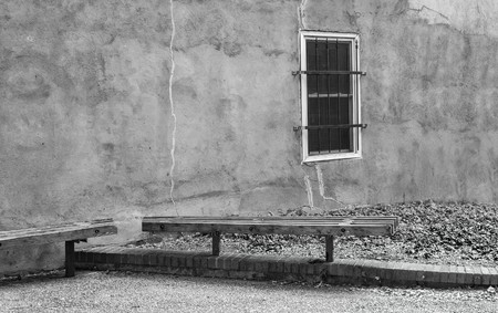 A black and white photo of a stucco wall in an alley way with two benches and a barred window.