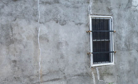A black and white photo of a stucco wall with a single barred window.