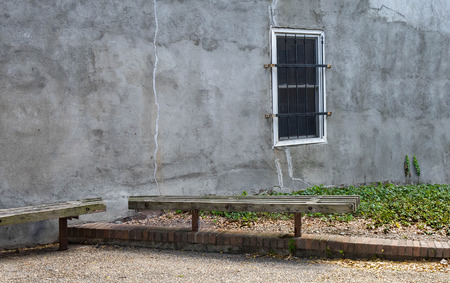 Stucco wall in an alley way with two benches and a barred window.