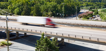 A semi truck crossing over a bridge taken with slow shutter speed to show movement and speed.