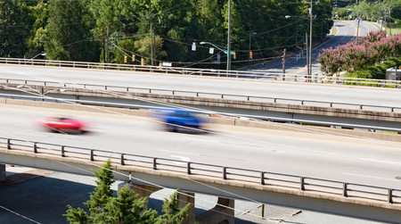 Two vehicles crossing over a bridge taken with slow shutter speed to show movement and speed.