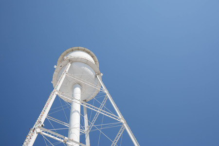 Looking up at a bright white water tower from below with a bright blue cloudless sky.