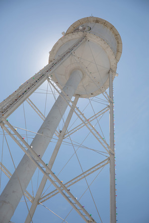 Looking up at a bright white water tower from below backlit with the sun and a bright blue sky.