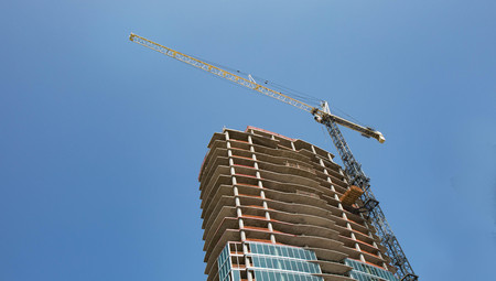 Construction of a new high rise building with a crane and bright blue sky for background.