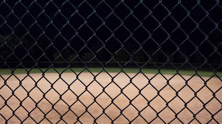 Close up photo of a baseball field fence looking through it to an empty field at night.  Great for background use. Stock Photo