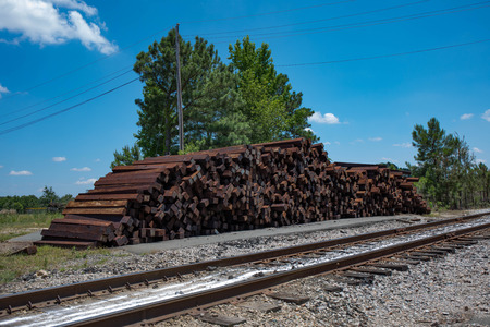 A large pile of unused railroad ties stacked beside the railroad tracks.  (high saturation)