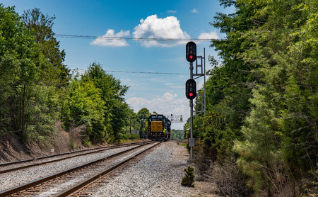 A long view of two railroad cars with flashing signals and an engineer standing on the back.  (high saturation)