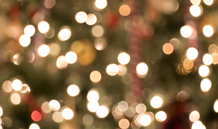 The sparkling lights on a christmas tree with soft focus so everything is blurred.
