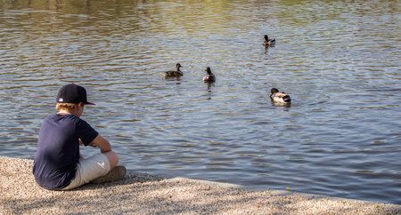 A boy reflecting on the edge of a pond while feeding the ducks.