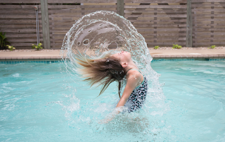 A 9 year old girl flipping her hair in a pool creating an arch of water over her head.