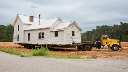 An old white house being transported on the back of a truck.