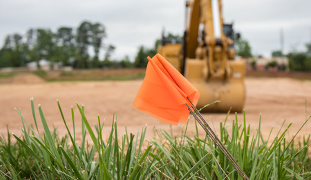 A bokeh close up shot of a warning flag at a construction site with an excavator in the background.